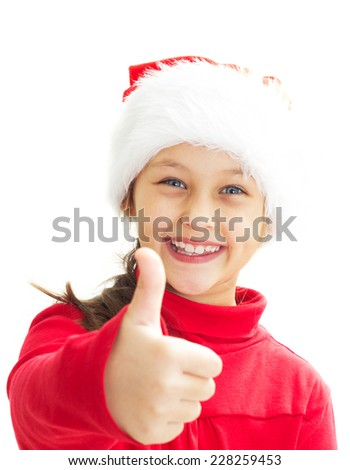 portrait of a smiling little girl in Santa hat showing thumb - stock photo