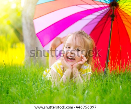 Portrait of a smiling little girl lying on green grass under the colorful umbrella. Cute child enjoying nature outdoors. Healthy carefree kid playing outside in summer park. Suntan protection - stock photo