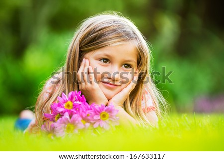 Portrait of a smiling little girl lying on green grass with flowers - stock photo