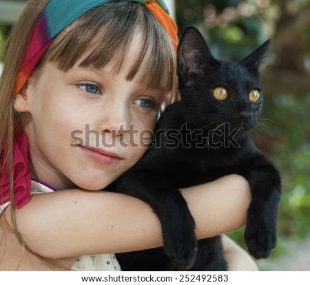 Portrait of a smiling little girl with cat - stock photo