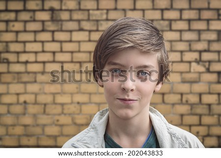 portrait of a smiling male teenager in front of a yellow brick wall. - stock photo
