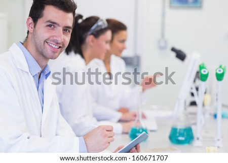 Portrait of a smiling male with researchers working on experiments in the laboratory - stock photo