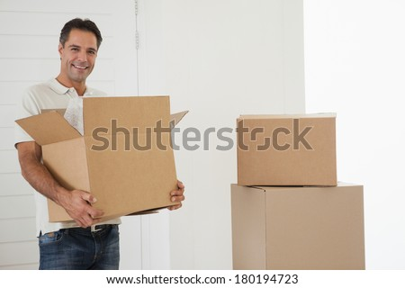 Portrait of a smiling man carrying boxes in new house - stock photo