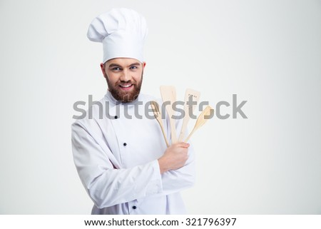 Portrait of a smiling man cook holding spoons isolated on a white background - stock photo