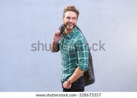 Portrait of a smiling man walking looking over shoulder - stock photo