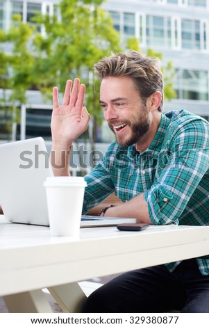 Portrait of a smiling man waving hello on chat with laptop - stock photo