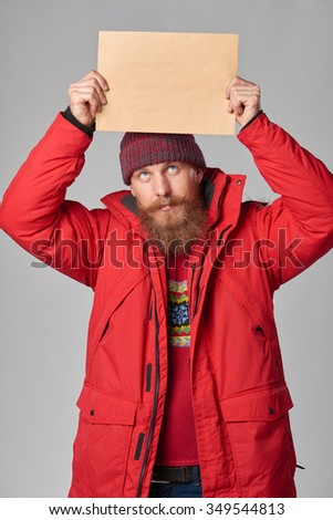 Portrait of a smiling man wearing red winter Alaska jacket showing big envelope - banner with copy space for text, looking at camera - stock photo