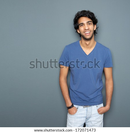 Portrait of a smiling man with hands in pocket standing against gray background - stock photo