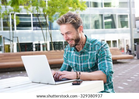 Portrait of a smiling man working on laptop outdoors - stock photo