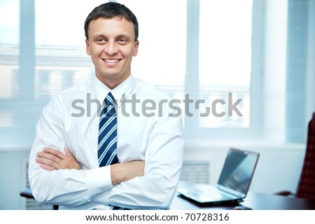 Portrait of a smiling manger with hands crossed at chest - stock photo