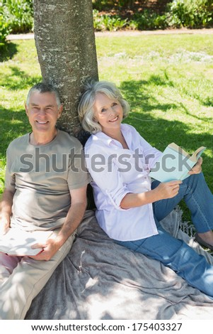 Portrait of a smiling mature couple sitting against a tree at the park - stock photo