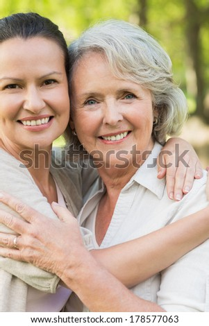 Portrait of a smiling mature woman with adult daughter at the park - stock photo