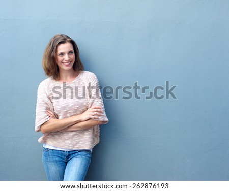 Portrait of a smiling mid adult woman standing with arms crossed on blue background - stock photo