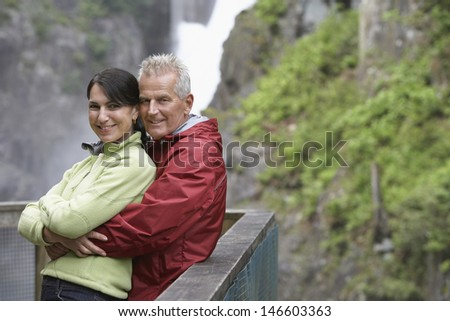 Portrait of a smiling middle aged couple against railing in mountains - stock photo
