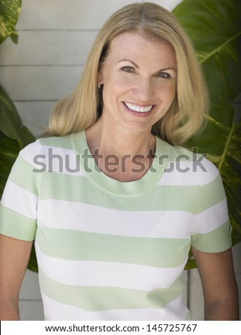 Portrait of a smiling middle aged woman standing against house wall - stock photo