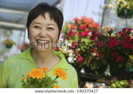 Portrait of a smiling middle aged woman with flowers in plant nursery - stock photo