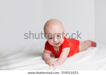 Portrait of a smiling 5 months baby boy in a red onesie lying down on a white blanket, holding hands together - stock photo