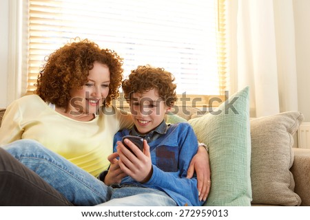 Portrait of a smiling mother and son relaxing at home - stock photo