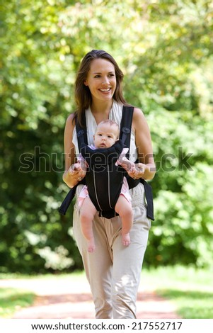 Portrait of a smiling mother walking outdoors with baby in sling - stock photo