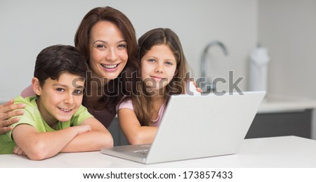 Portrait of a smiling mother with young kids using laptop in the kitchen at home - stock photo
