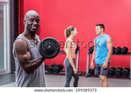 Portrait of a smiling muscular man lifting a dumbbell - stock photo