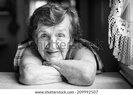 Portrait of a smiling old woman (black and white photo) - stock photo