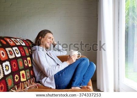 Portrait of a smiling older woman relaxing at home with cup of tea - stock photo