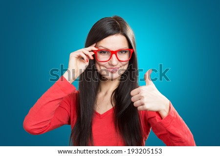 Portrait of a smiling pretty girl with a thumb up, studio shot on blue background  - stock photo