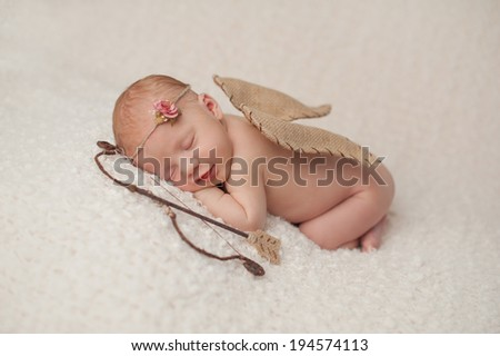 Portrait of a smiling, red headed, 2 week old, newborn baby girl. She is wearing a Cupid costume with angel wings, bow and arrow and is sleeping on a cream colored blanket. - stock photo