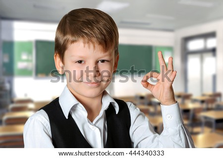 Portrait of a smiling schoolboy  showing ok sign. Education and school concept - stock photo