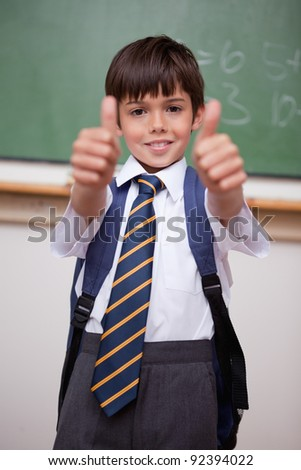 Portrait of a smiling schoolboy with the thumbs up in a classroom - stock photo