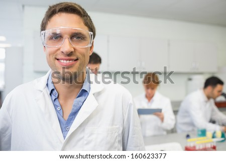 Portrait of a smiling scientist with colleagues at work in the laboratory - stock photo