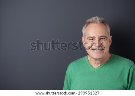 Portrait of a Smiling Senior Man in Casual Green Shirt Against Gray Wall Background with Copy Space on the Left Side. - stock photo