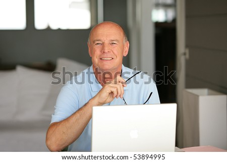 Portrait of a smiling senior man in front of a laptop computer - stock photo
