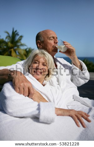 Portrait of a smiling senior woman and a senior man drinking a glass of water - stock photo
