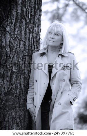 Portrait of a smiling senior woman leaning on a tree - stock photo