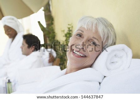 Portrait of a smiling senior woman relaxing at spa in bathrobe - stock photo