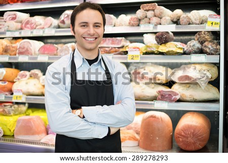 Portrait of a smiling shopkeeper in a grocery store - stock photo