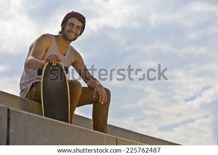 Portrait of a smiling skateboarder, sitting on concrete steps, seen from below - stock photo
