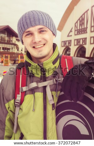 Portrait of a smiling snowboarder at a ski resort. Toned image. - stock photo