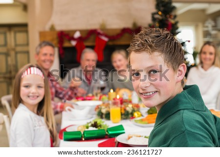 Portrait of a smiling son with his family behind him at home in the living room - stock photo