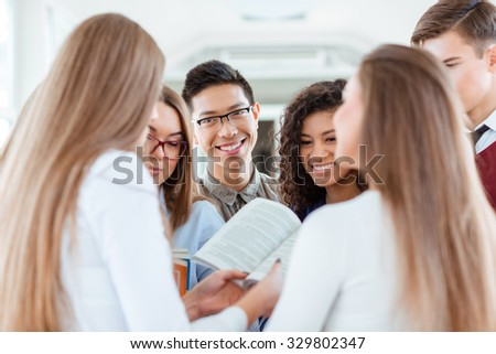 Portrait of a smiling students speaking about book in university hall - stock photo