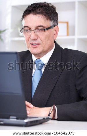 Portrait of a smiling successful business man using a laptop at work in office - stock photo