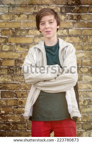 portrait of a smiling teenage boy with crossed arms - stock photo