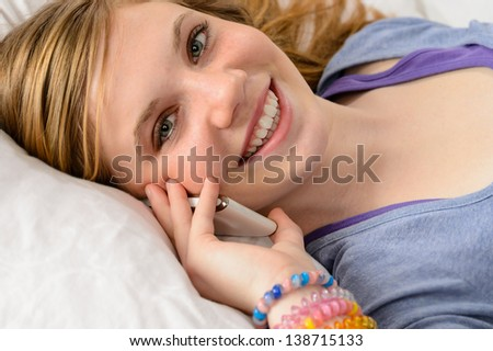 Portrait of a smiling teenager girl talking on her phone - stock photo