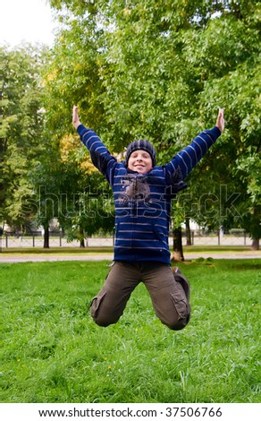 portrait of a smiling teenager jumping in the park - stock photo