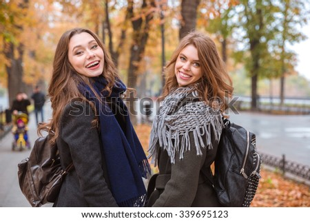 Portrait of a smiling two girlfriends walking in autumn park and looking back at camera - stock photo