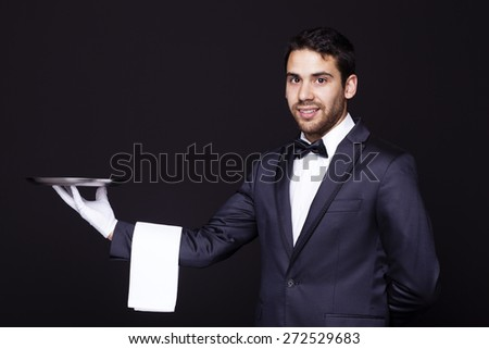Portrait of a smiling waiter holding an empty silver tray against dark background - stock photo