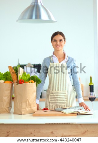 Portrait of a smiling woman cooking in her kitchen - stock photo