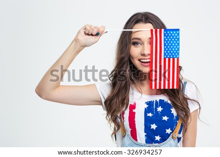 Portrait of a smiling woman covering her eye with USA flag isolated on a white background - stock photo